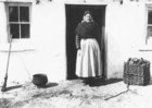Aran woman standing at the door of a cottage_thumb.jpeg